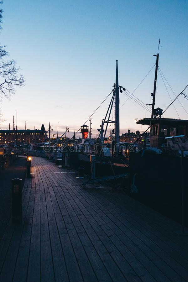 Walking down a small pier at sunset with lots of small boats, Stockholm Sweden royalty free stock photography