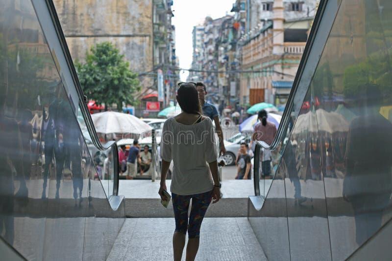 Walking in downtown Yangon, Burma. Woman walks between escalators towards the streets of downtown Yangon royalty free stock photography