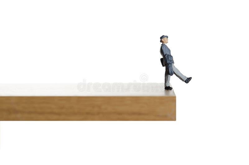 Walking on the edge. Business figurine walking off a ledge stock photo