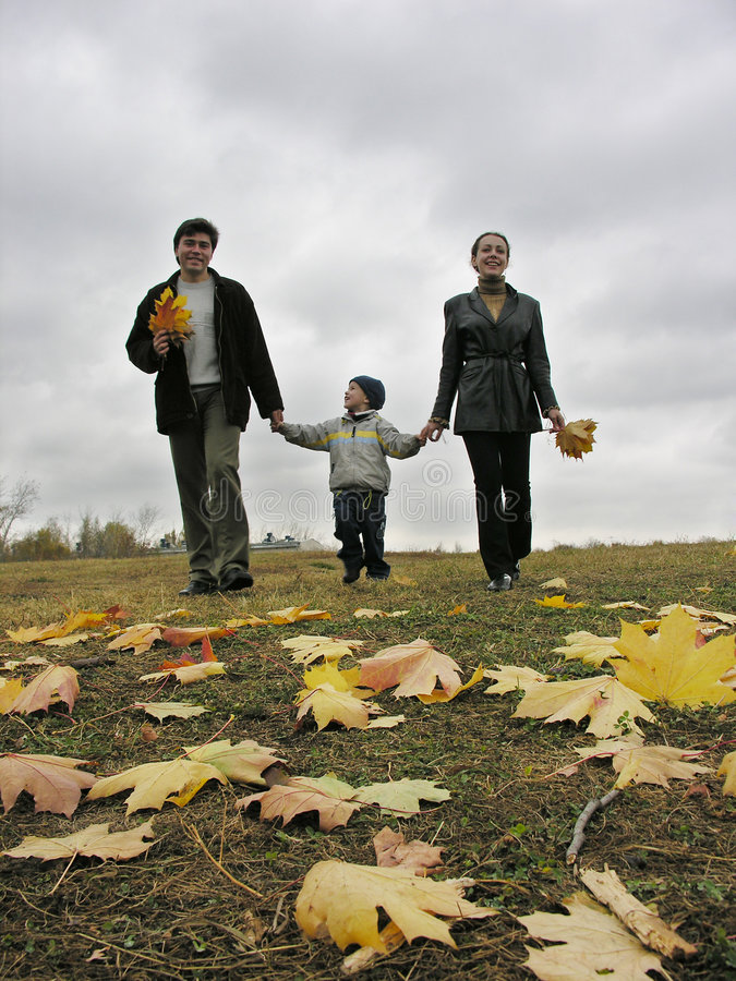 Walking family with autumn leaves and clouds stock images