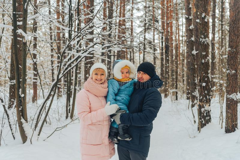 Walking family with a child. Family walks in nature in winter. Winter family walk in nature. A lot of snow stock images