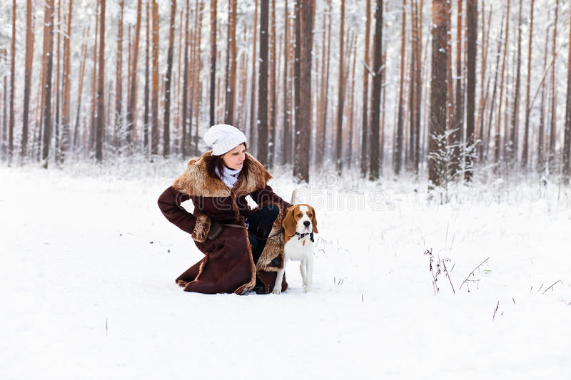 Walking in forest. The woman on winter walk with a dog stock images