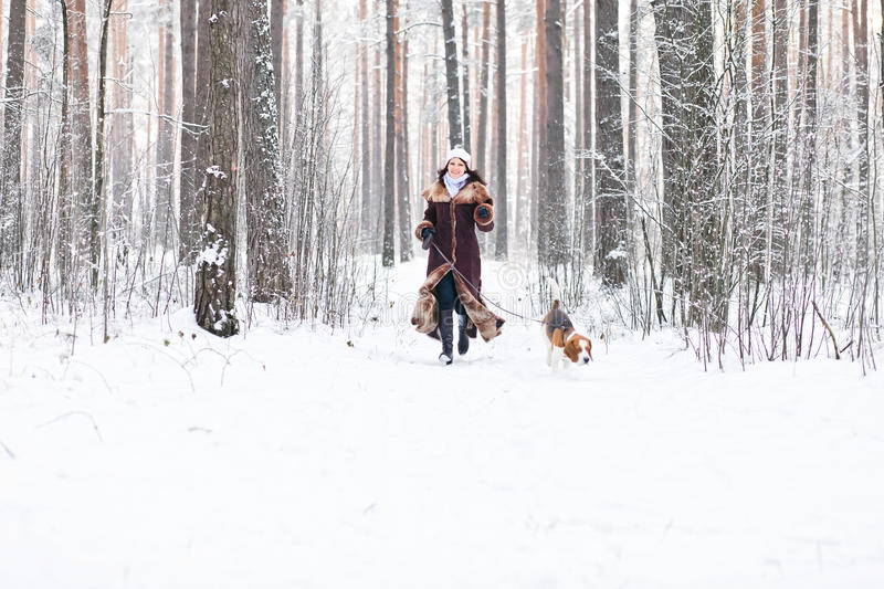Walking in forest. The woman on winter walk with a dog royalty free stock photography