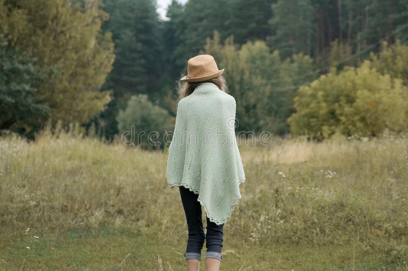Walking girl child in hat knitted blanket boots, back view stock photography