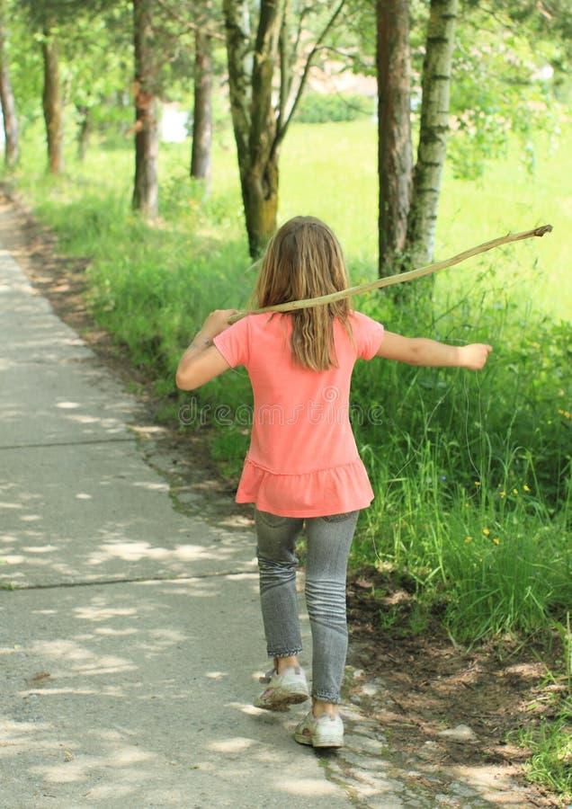 Walking girl. Little girl in pink t-shirt and grey trousers walking on grey beton street royalty free stock image