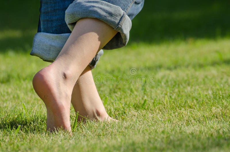 Walking on grass. Girl's legs walking in the grass stock photography