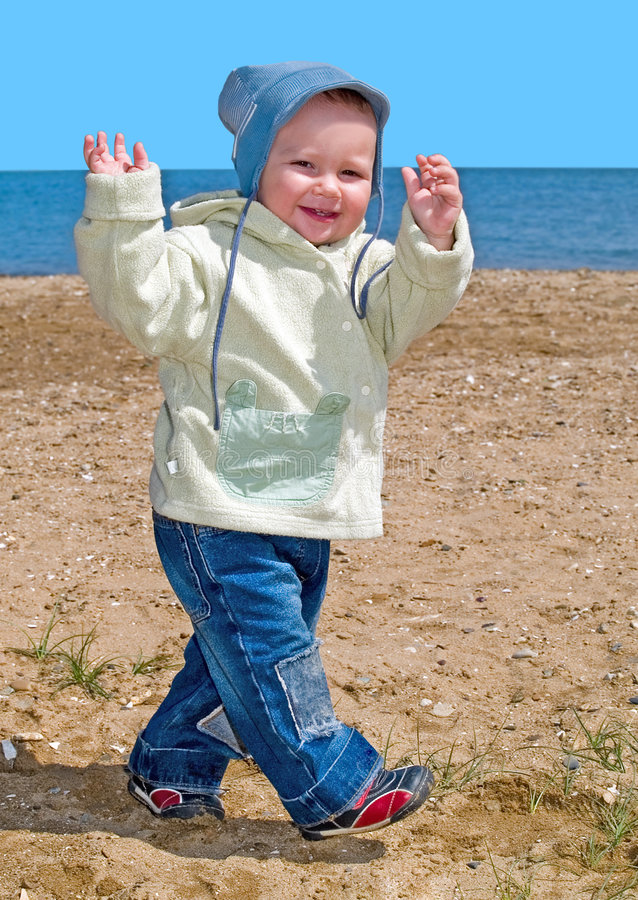 Walking happy boy on the sea beach stock images