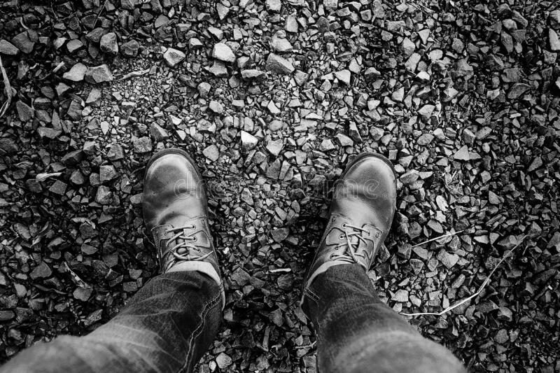 Walking and leaving footprints with a textured background of black and white rocks ... magical. Hiking boots ideal for walking and leaving footprints with a stock images