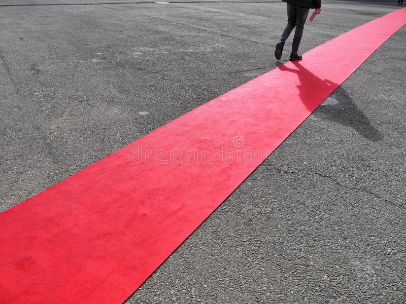 Walking lonely man on red carpet close view on legs. Walking lonely man and shadow on red carpet close view on legs stock images