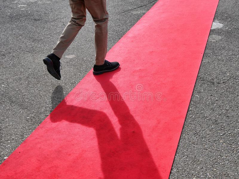 Walking lonely man on red carpet close view on legs. Walking lonely man and shadow on red carpet close view on legs stock photo