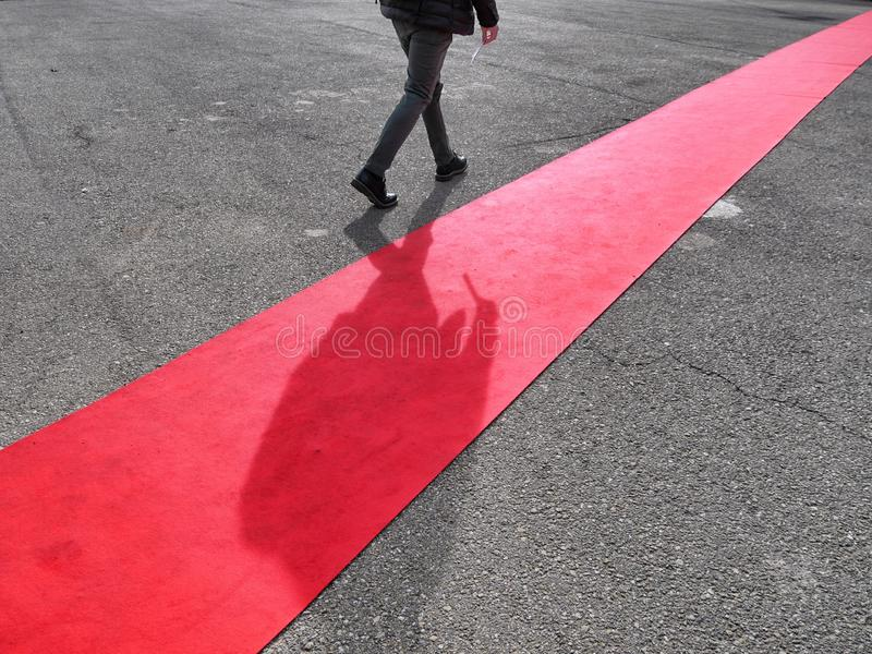 Walking lonely man on red carpet close view on legs. Walking lonely man and shadow on red carpet close view on legs royalty free stock photos