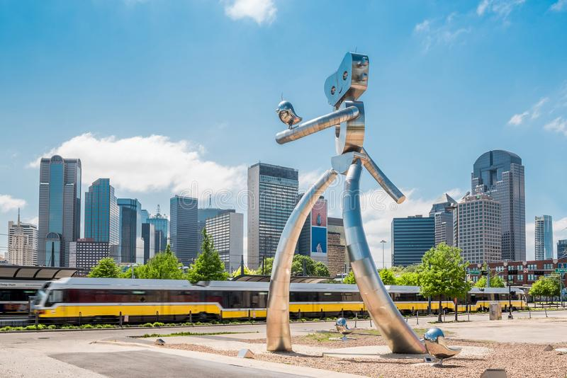 Walking man statue Dallas Texas with skyline and train royalty free stock photos