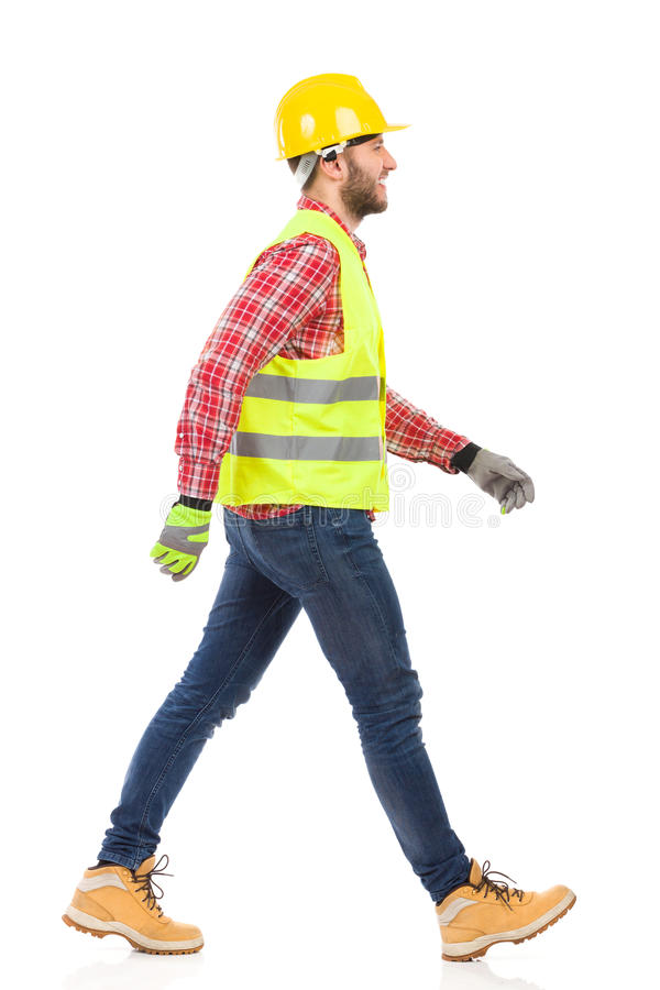 Walking manual worker. Walking construction worker in yellow helmet and lime reflective vest. Full length studio shot isolated on white stock photo