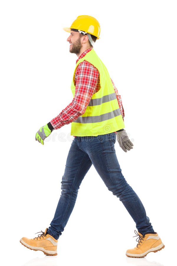 Walking mechanic. Walking construction worker in yellow helmet and lime reflective waistcoat. Full length studio shot isolated on white royalty free stock images