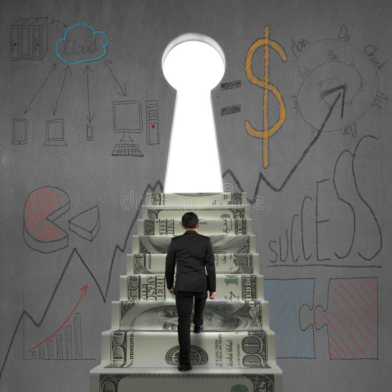 Walking on money stairs to key door with business dooles. Man walking on money stairs to key shape door with business dooles on wall royalty free stock image