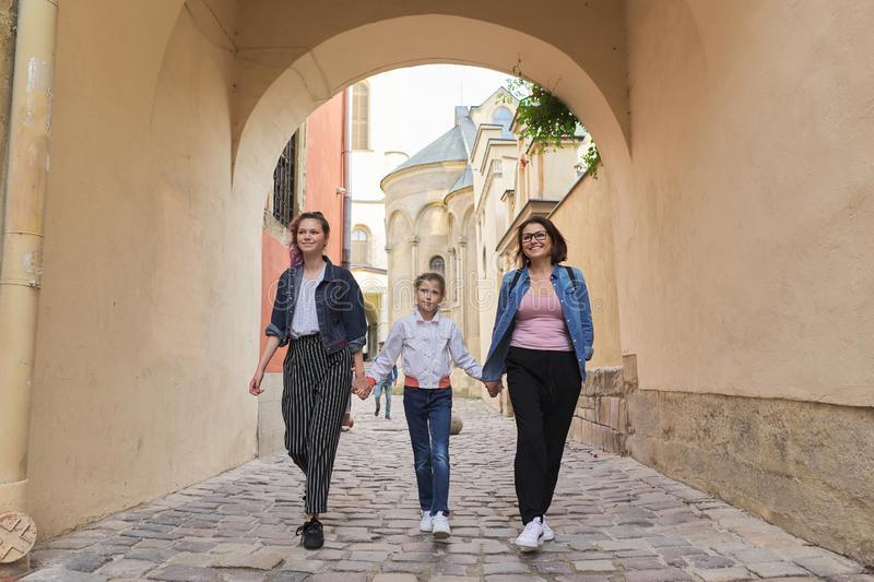 Walking mother and two daughters holding hands royalty free stock photos