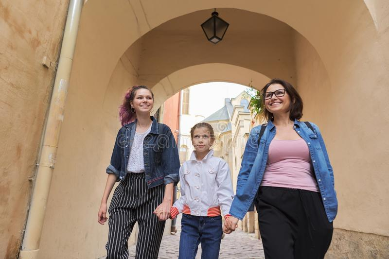 Walking mother and two daughters holding hands royalty free stock images