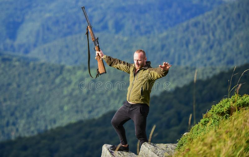 Walking in mountains. Hunting masculine hobby concept. Regulation of hunting. Hunter hold rifle. Nice day for hunt stock image