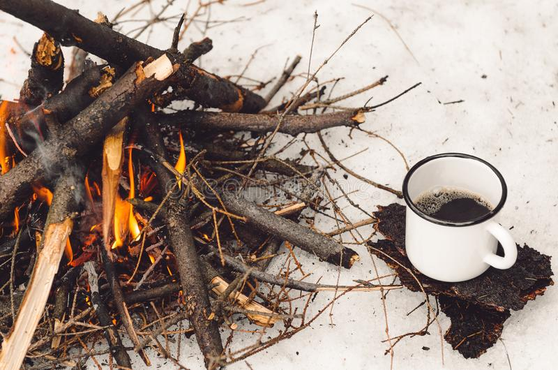 Walking mug with coffee near the campfire. Concept hike, walk, trip in winter stock images