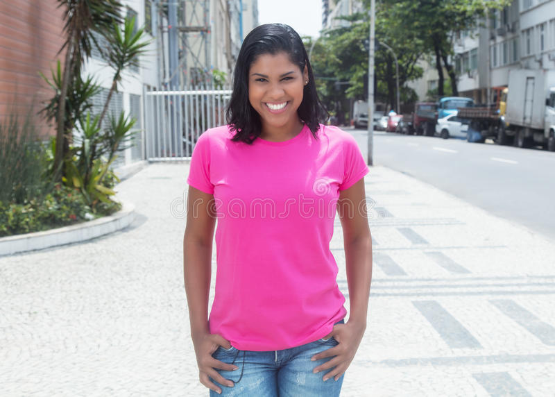 Walking native latin woman in a pink shirt in city. In the summer stock photography