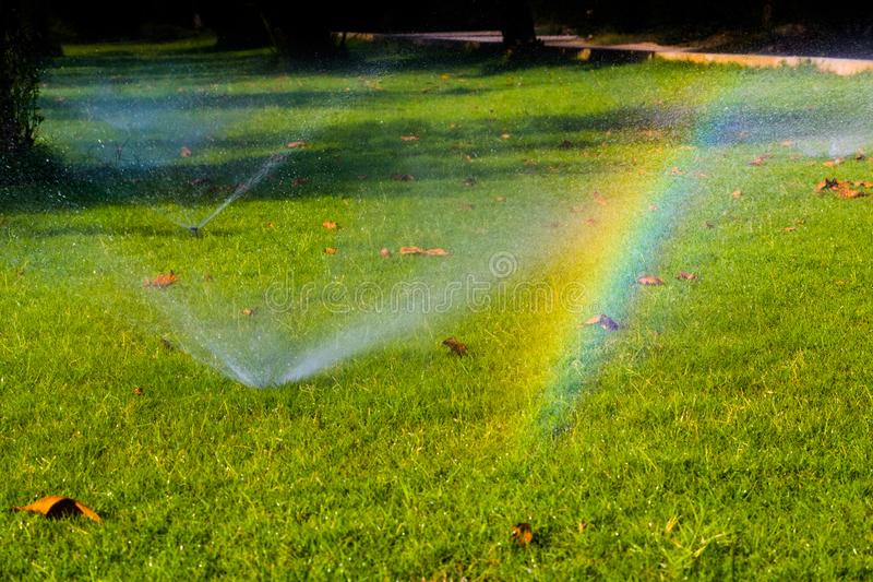 An unexpected rainbow appears!. Walking near the grass watering system a rainbow appears as the angle of the sun light being refracted in the water particles stock photography
