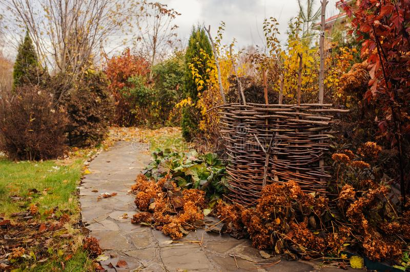Walking in november garden. Late autumn view with rustic fence. And stone pathway stock photo