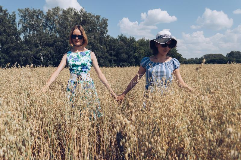 Walking through oat field female friends stock photos