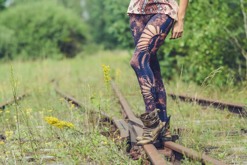 Walking on old abandoned railway, legs in colorful tights stock images