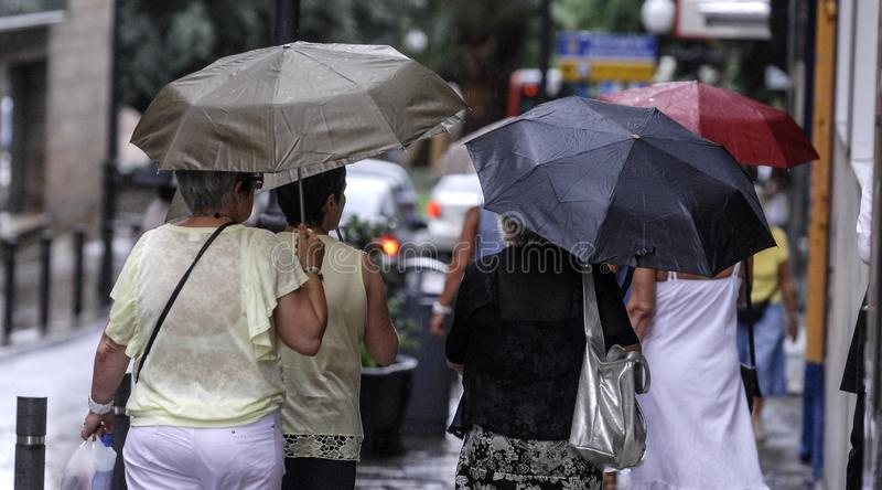 Women walk with their umbrellas stock photo