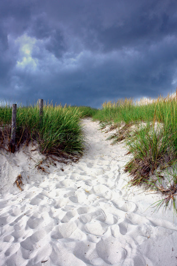 Walking Path over Sand Dune under Stormy Sky. Foot path winding into sand dunes with tall grass leading to the beach at the shore under a cloudy and stormy stock photo