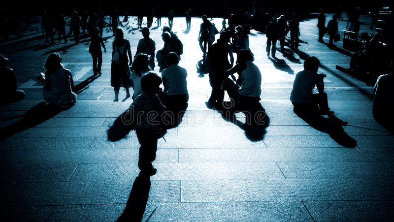 Walking people silhouettes blue tint. High contrast and deep shadows royalty free stock photo