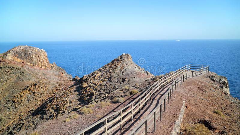 Walking platform on cliff edge, overlooking blue ocean . Walking path to the edge of the cliff on top of rocky mountain, with panoramic view over Atlantic Ocean royalty free stock photography
