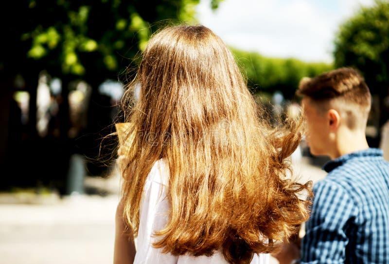 Walking on promenade. Rear view of two walking teenage couple on promenade royalty free stock image