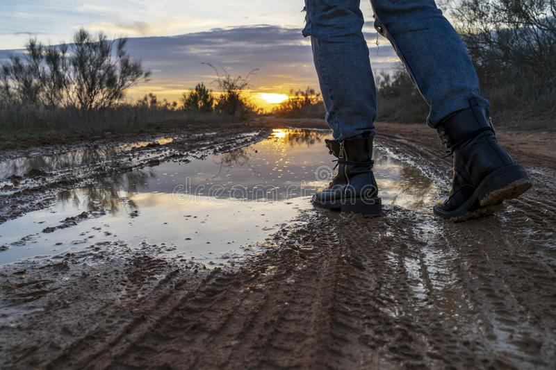 Walking through a puddle with military boots. Walking through a puddle with military boots with the sunset reflected royalty free stock photography
