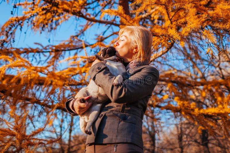 Walking pug dog in autumn park. Happy woman hugging and kissing pet. Outdoors royalty free stock image