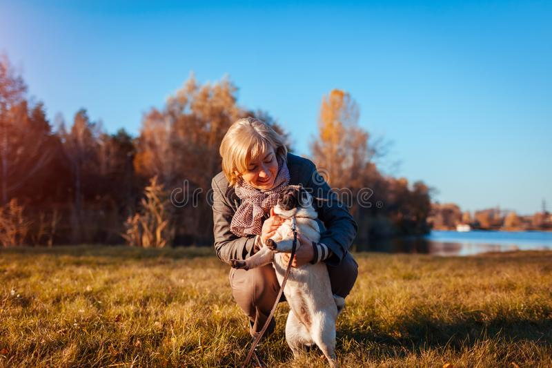 Walking pug dog in autumn park by river. Happy woman hugging pet and having fun with best friend. Outdoors royalty free stock photography