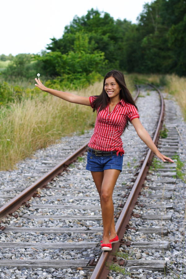 Walking on rails. Beautiful young mixed race woman balancing on railway tracks / rails. From Denmark stock photos