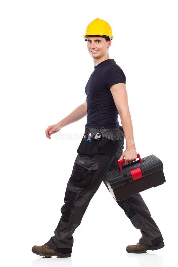 Walking repairman carrying toolbox royalty free stock photography