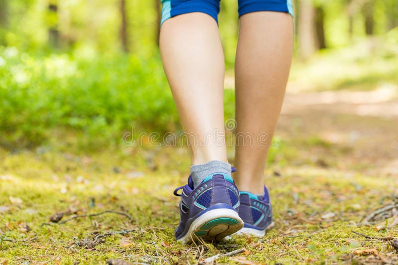 Walking or running legs in forest, exercising in summer nature.Training outside in summer and fitness concept. royalty free stock image