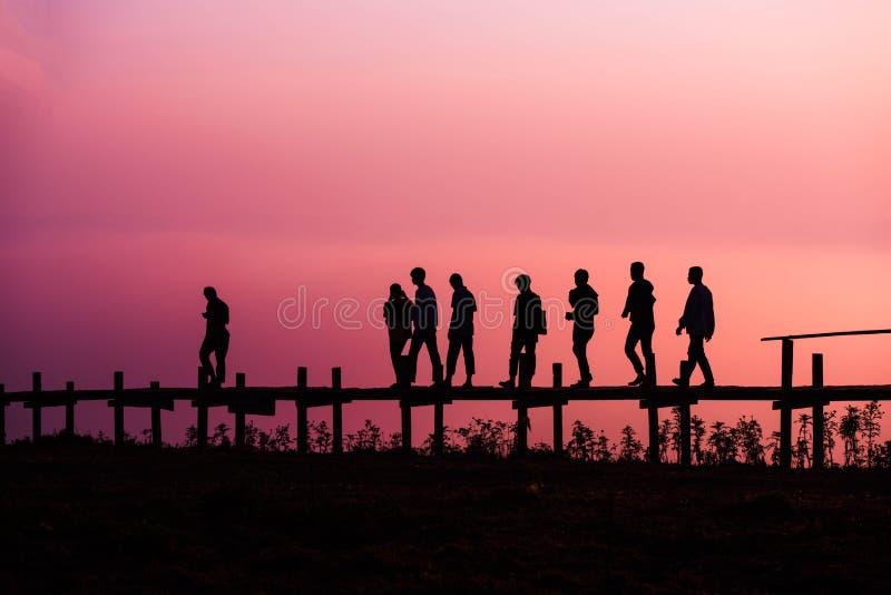 Walking Silhouette Sunset. Group Boys Walking on Wood bridge Sunset Silhouette stock image