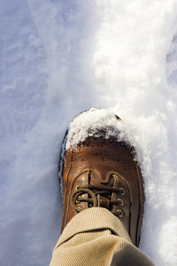 Walking In Snow. Closeup of leather shoe walking in snow royalty free stock photos