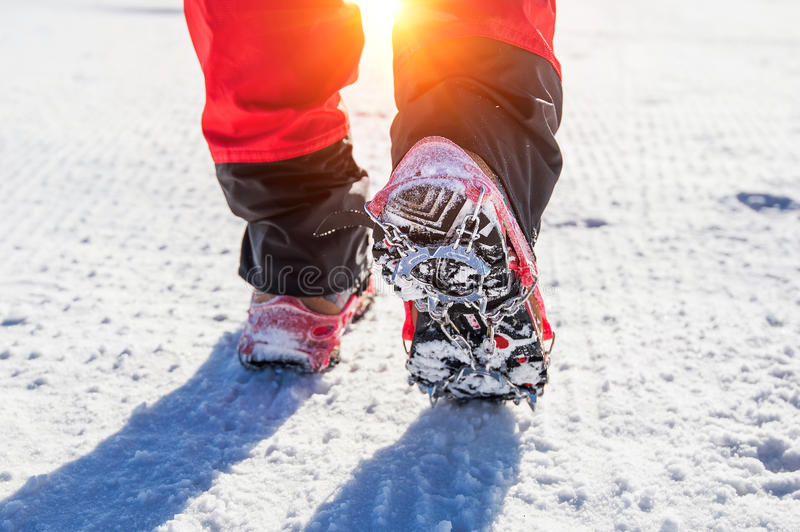 Walking on snow with Snow shoes and Shoe spikes in winter. View of walking on snow with Snow shoes and Shoe spikes in winter stock photo