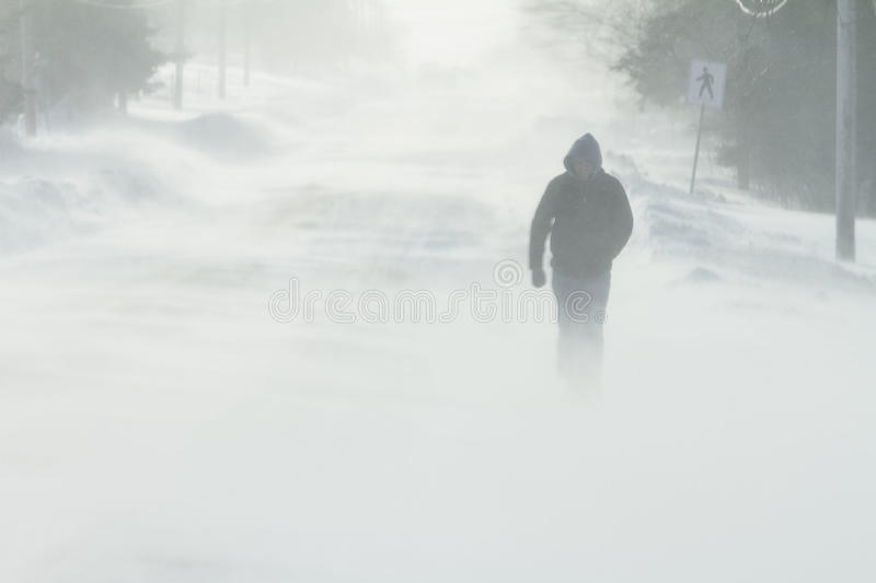Walking in Snow Storm. A pedestrian walks through a snow storm stock images