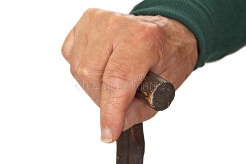 Walking stick in hand. Hands of old man with walking stick - detail shot stock photography