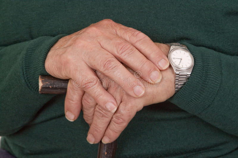 Walking stick in hands. Hands of old man with walking stick - detail shot royalty free stock photo