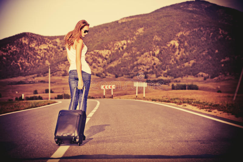 Walking with suitcase. Attractive young woman hitchhiking along a road stock image