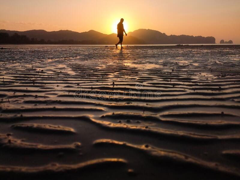 Walking into sunrise on morning on a sandy beach with mountains in the background. Man walking into sunrise on morning on a sandy beach with mountains in the stock photography