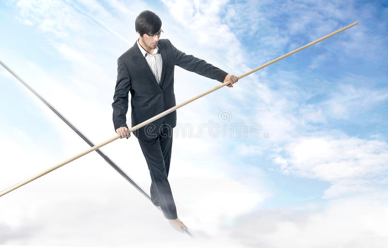 Walking a tightrope. Handsome businessman walking a tightrope royalty free stock images