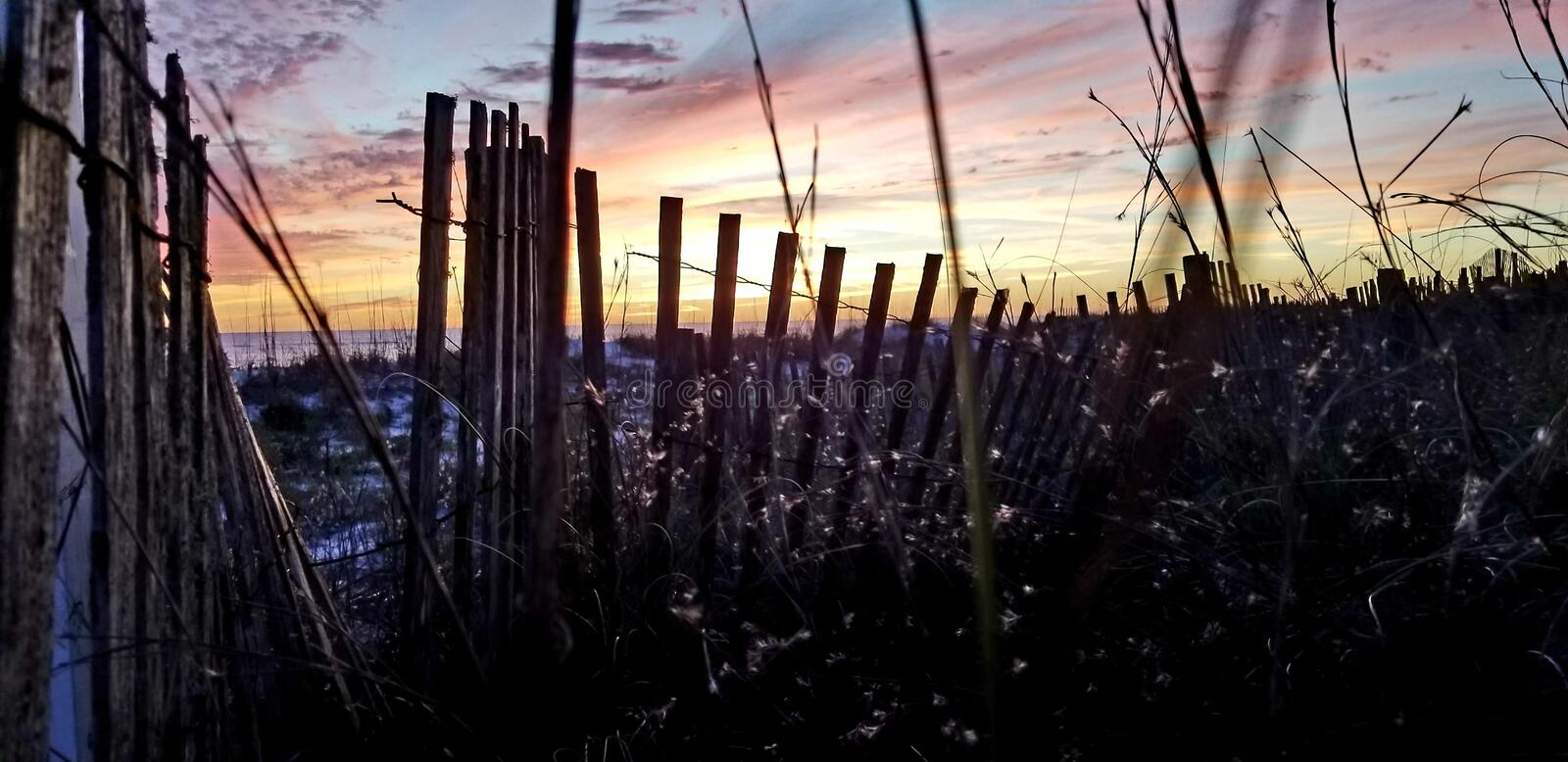 A walk to the beach. Walking to the prettiest beaches and watching the sunset. Sunset looking through a old wooden fence stock image