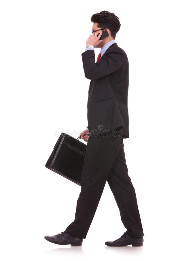 Walking to side & talking on phone stock photo